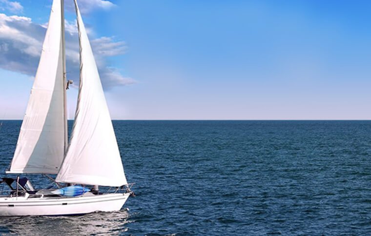 White sailboat sailing in the ocean near Plymouth, England