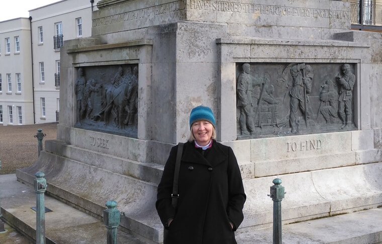 Woman with a coat and winter hat on posing near the Scott Memorial in Plymouth, England
