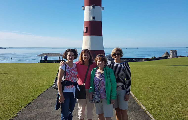 Group of four women posing in front of the Plymouth Hoe lighthouse