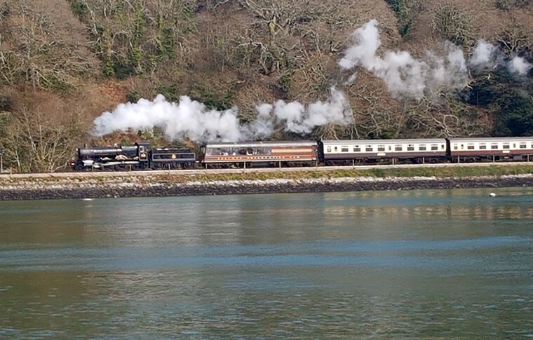 Steam engine train traveling along the coast in Dartmouth